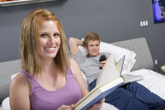 Happy Woman Reading Novel In Bedroom Royalty Free Stock Photos