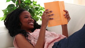 Happy woman reading a novel. In her living room stock video