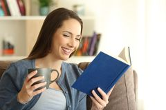 Happy woman reading a paper book alone at home royalty free stock images