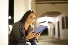 Happy woman reading a book in the night in the street. Happy woman reading a paper book sitting in the night in the street stock photo