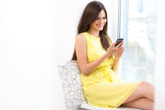 Happy Woman Reading sms on her Mobile Phone. Royalty Free Stock Photo