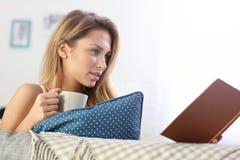 Happy woman reading on sofa Stock Image