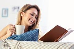 Happy woman reading on sofa Royalty Free Stock Photos