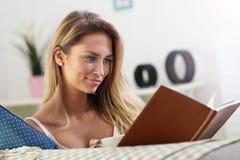 Happy woman reading on sofa Stock Photos