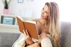 Happy woman reading on sofa Stock Photography