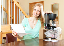Happy woman reading  warranty card for new coffee machine Royalty Free Stock Photos