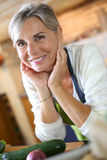 Happy woman ready to cook in kitchen Royalty Free Stock Images