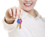 Happy woman real estate agent holding set of keys to new house. Or car. Property business and accomodation or home buying ownership concept, isolated on white Stock Photo