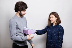 A happy woman receiving a present from her boyfriend. A stylish boy dressed in casual sweater giving her girlfriend a present for Stock Photos