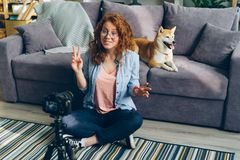 Happy woman recording video about dogs at home using professional camera. Happy young woman is recording video about pedigree shiba inu dogs at home using royalty free stock images