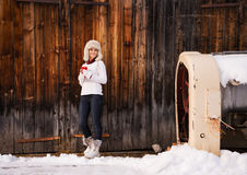 Happy woman with red cup in front of rustic wood wall Royalty Free Stock Photo