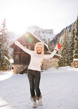 Happy woman with red cup rejoicing near cosy mountain house Royalty Free Stock Photography