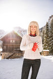 Happy woman with red cup standing near cosy mountain house Stock Image