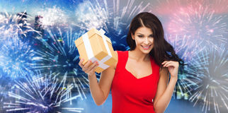 Happy woman in red dress with gift over firework Stock Photography