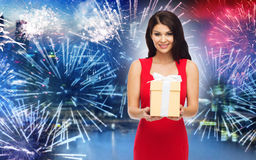 Happy woman in red dress with gift over firework Stock Photos