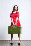 Happy woman in a red dress holding a suitcase Stock Photography
