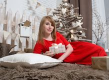 Happy woman in a red dress is lying on a soft carpet with a gift in her hands. Christmas decoration and Christmas tree in the background Stock Photography