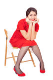 Happy woman in red dress sitting on a chair Stock Image