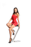 Happy woman in red dress sitting on chair Stock Photo