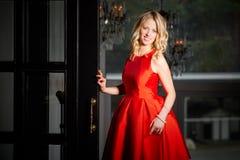 Happy woman in red dress standing next to door Stock Photography