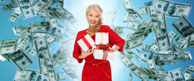 Happy woman in red with gifts over money rain Stock Images