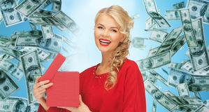 Happy woman in red with gifts over money rain Stock Photography