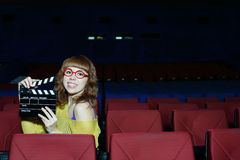 Happy woman in red glasses holds clap board Stock Image