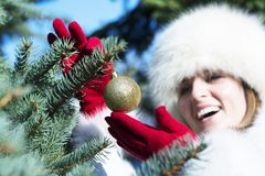 Happy woman with red gloves hanging golden bauble Royalty Free Stock Photos