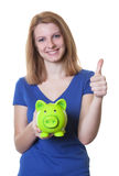 Happy woman with red hair and piggy bank showing thumb up Stock Photography
