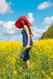 Happy woman in a red hat with a bouquet of wildflowers. Beautiful happy woman in a red hat with a bouquet of wildflowers in a field of alfalfa on a blue sky Royalty Free Stock Photos