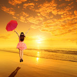 Happy Woman red holding umbrella and Jumping in Sea Sunset Stock Image