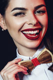 Happy woman with red lips holding wooden bow tie Stock Photos