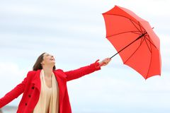 Woman playing with an umbrella in winter on the beach. Happy woman in red playing with an umbrella in winter on the beach royalty free stock photo