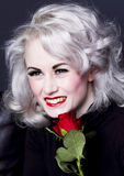 Happy woman with red rose. Attractive, platinum blonde woman holding a red rose and smiling Royalty Free Stock Photo