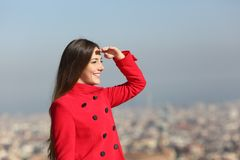Happy woman scouting in winter with urban background. Happy woman in red scouting with hand on forehead in winter with urban background royalty free stock photo