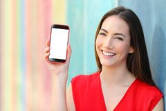 Happy woman in red showing at camera smart phone screen royalty free stock image