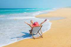 Happy woman  in red sunhat on the beach. Happy woman  in red sunhat on the morning beach sitting on deckchair with hands up.Vacation and travel concept Royalty Free Stock Photo