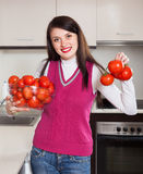 Happy  woman with red tomatoes in  kitchen Stock Images