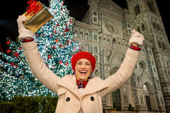Happy woman rejoicing near Christmas tree in Florence, Italy. Happy young woman in white coat with gift box rejoicing in front of Christmas tree near Duomo in royalty free stock images
