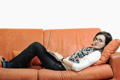 Happy woman relax on orange sofa Stock Image