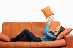 Happy woman relax on orange sofa Royalty Free Stock Images