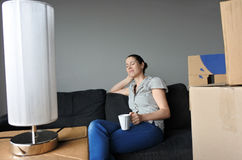Happy woman relax on a sofa during a move into a new home. Happy woman (age 30-35) relax on a sofa during a move into a new home. Moving house concept. Real Stock Photo