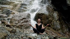 Woman practicing yoga at waterfall with headphones stock video footage