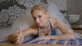 Happy woman relaxes in Turkish bath and show a thumb up stock footage