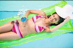 Happy woman relaxing on air bed in swimming pool. Happy woman in bikini lying on air bed in swimming pool with a glass of cocktail Stock Photo