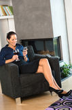 Happy woman relaxing armchair text messaging wine Stock Photography