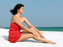 Happy Woman Relaxing on a Beach. Young happy woman relaxing on a beach Royalty Free Stock Image