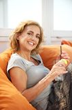 Happy woman relaxing with a drink at a restaurant Stock Photos