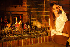 Happy woman relaxing at fireplace. Winter home. Royalty Free Stock Images