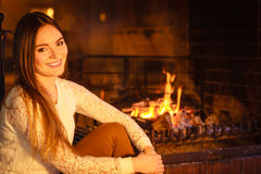 Happy woman relaxing at fireplace. Winter home. Stock Photography